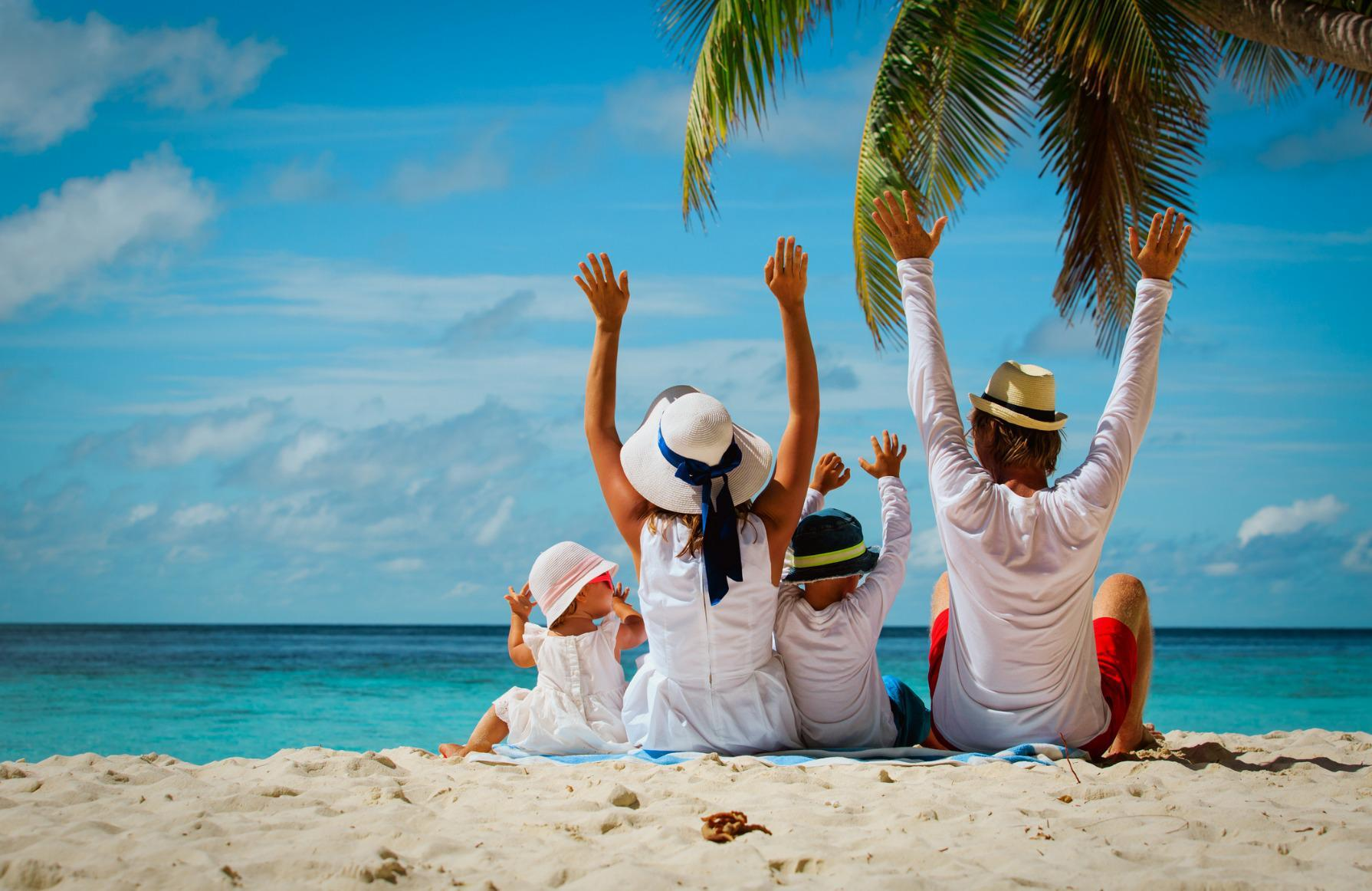 happy-family-with-two-kids-hands-up-on-beach-picture-id677652068_0