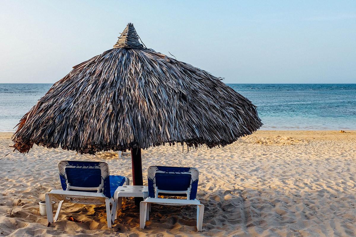 Beach loungers under a palapa ath the beach